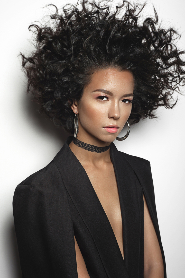 Fashion studio portrait of beautiful mulatto woman with afro curls hairstyle. Fashion and style. Beauty and health