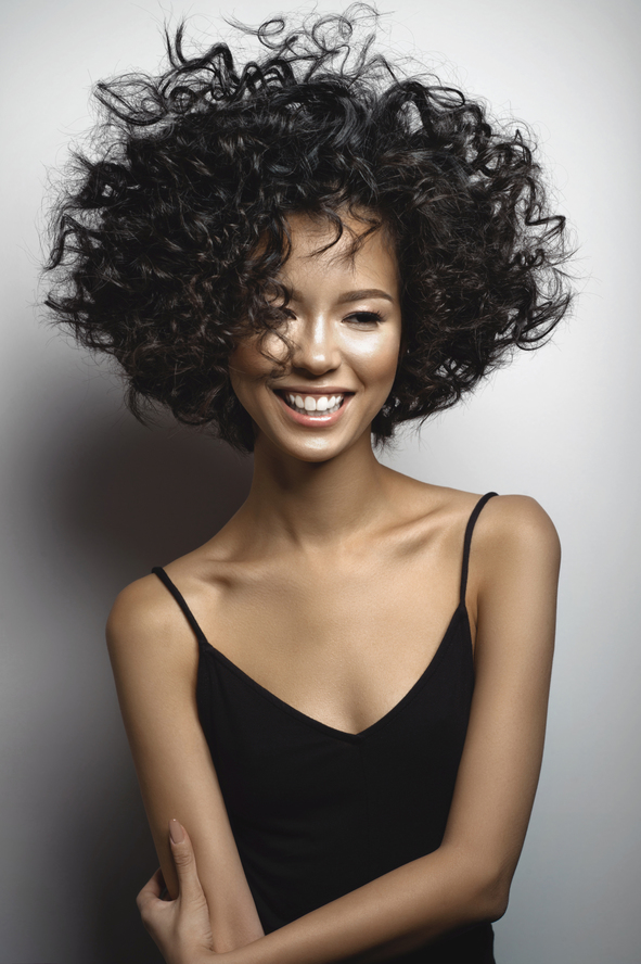 Fashion studio portrait of beautiful smiling woman in black dress with afro curls hairstyle. Fashion and beauty